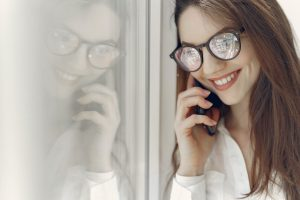 happy-young-woman-speaking-on-smartphone-near-window-4149069